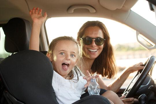 Donna al volante con maglietta bianca in contesto vacanziero viaggia con la figlia con espressioni sorridenti salutando qualcuno in lontananza