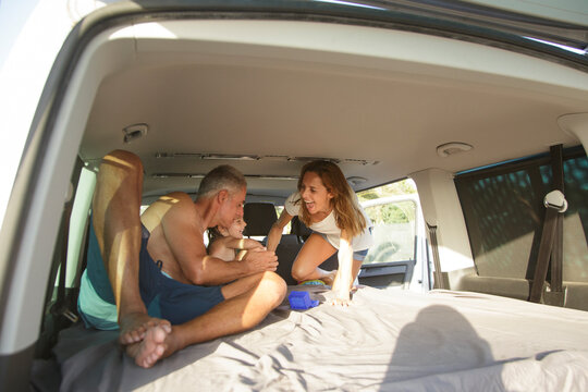famiglia felice composta da papà mamma e figlia, in abbigliamento da mare si abbraccia felice dentro al furgone parcheggiato in strada