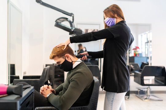 hairdresser cutting hair with razor to young man