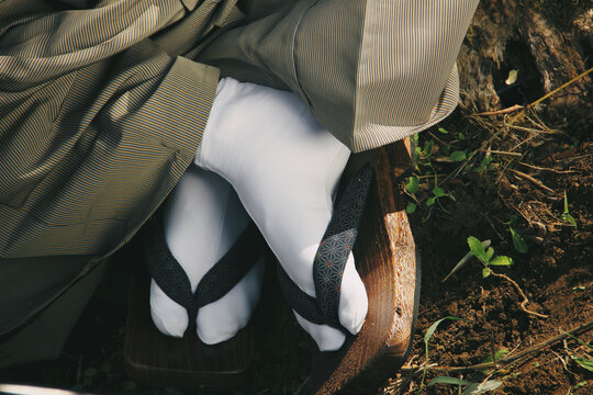 samurai feet with sandals and white socks on ground