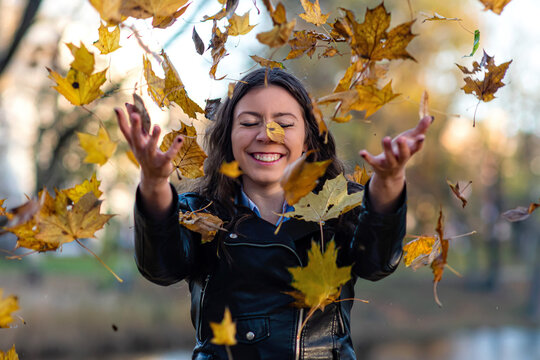 attractive woman is throwing up yellow maple leaves into the air