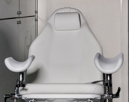 White gynecological chair in the gynecological office on a gray background.