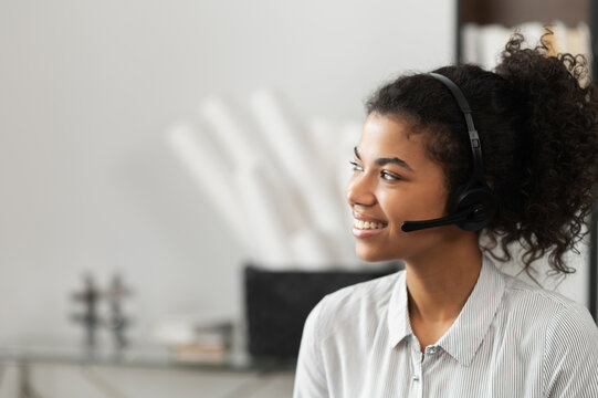 Young thoughtful African American female sudent in a headset is listening to an online webinar, studing remotely from home or working in the customer service department as a call center operator