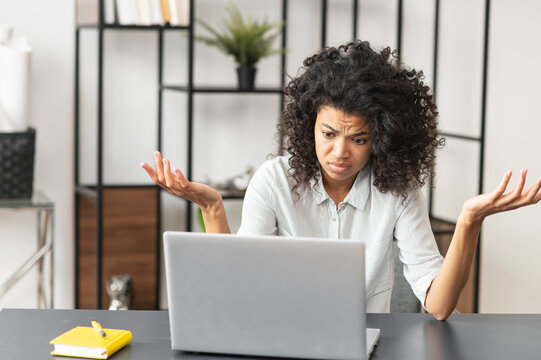 Young African American female office worker manager feeling stressed, tired, and overworked, does not know how to fix a problem, sitting at the desk in front of laptop, struggling and raising hands up