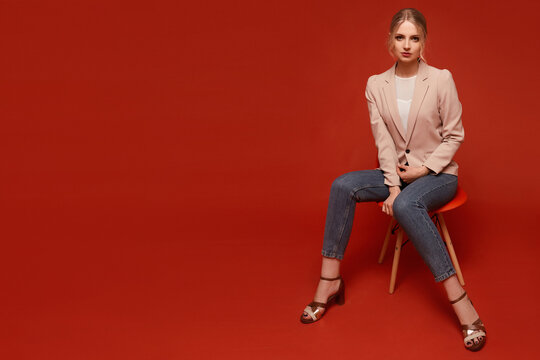 Nice-looking attractive young model woman wearing a beige blazer and jeans sitting on the chair, isolated over red background