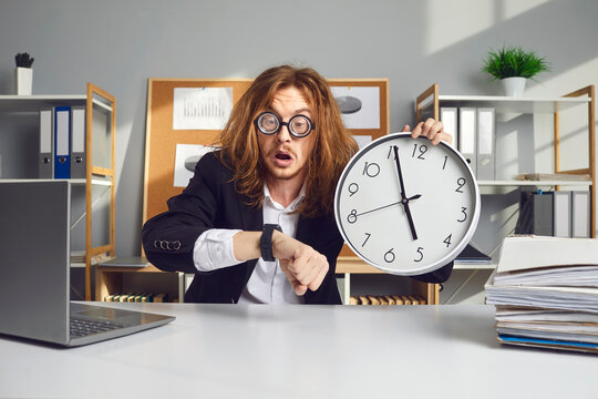 Employee working under pressure. Funny stressed young office worker with messy long hair holding clock, looking at wristwatch and panicking over missed deadline or being terribly late for work meeting