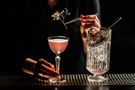 close-up of glass with pink alcoholic drink which woman decorates with sprig of white flower