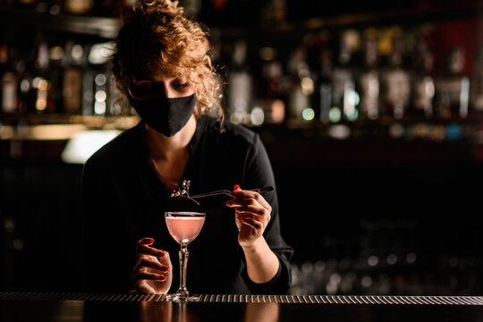 view of woman bartender in mask that neatly decorates glass of cocktail with flower sprig