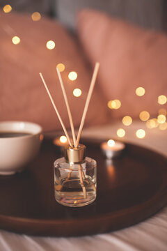 Home liquid perfume in glass bottle with sticks on tray with cup of tea in bed close up. Good morning. Cozy atmosphere conept.