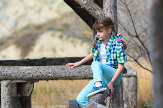 A girl tries to sit on a fence made of a thick wooden frame