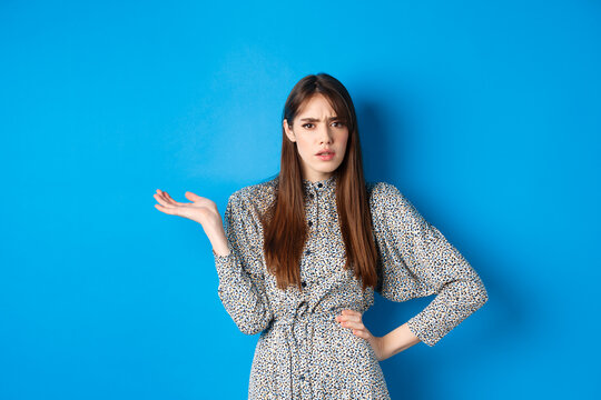 Confused and annoyed girl arguing, raising hand up and frowning, cant understand what big deal, standing on blue background