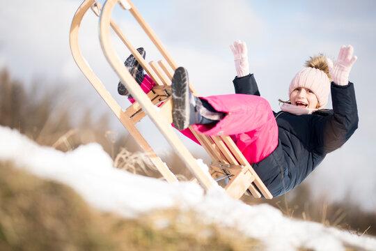 Little girl enjoying a sleigh ride. Child sledding.