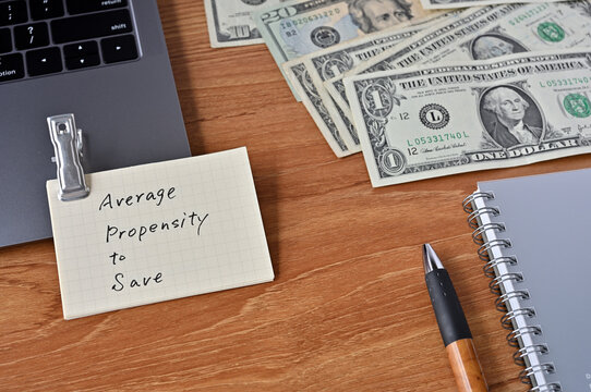 On the desk there are bills, a laptop, and memos with the word average propensity to save written on it.