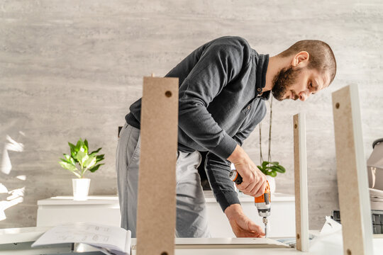 One Man with beard alone Putting Together Self Assembly Furniture at Home holding electric screwdriver looking the instructions - half length front view DIY concept real people copy space