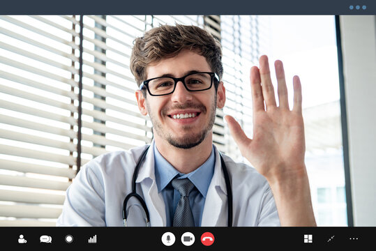 Young male doctor waving hand greeting patient online via video call, home medical consulation service concepts