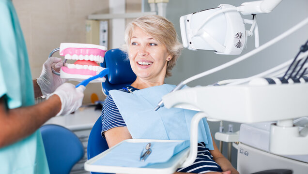 Male dentist explaining future treatment to female patient on dental model