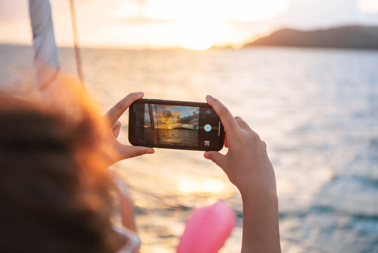 woman using a mobile phone Take pictures of the sunset on a boat on the sea.