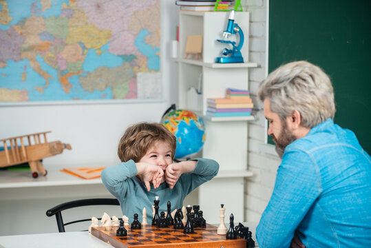 Dad with his child son are playing Chess. Teacher and schoolboy playing chess in class. Educational games.
