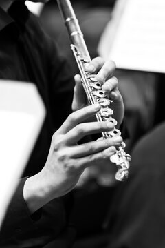 Flute in the hands of a musician in black and white