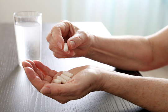 Elderly woman with pills in wrinkled hands. Medication in capsules, taking sedatives or vitamins