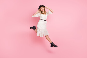 Wall Mural - Full length photo of carefree lady jump wear retro cap dotted dress boots isolated pink color background