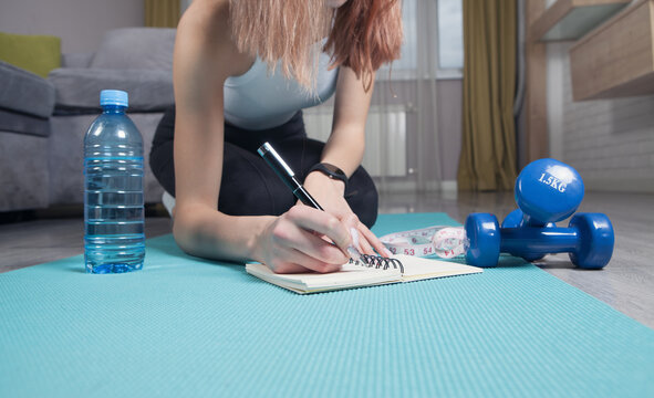 Young woman sitting in mat writes training plans at home.