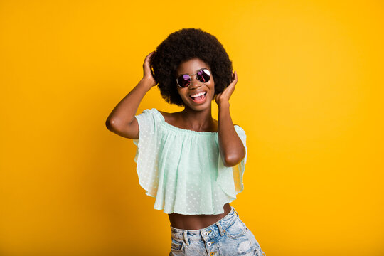 Photo portrait of woman touching hair isolated on vivid yellow colored background
