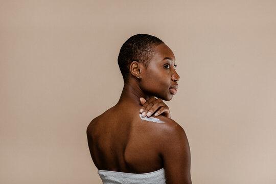 Black woman applying body cream