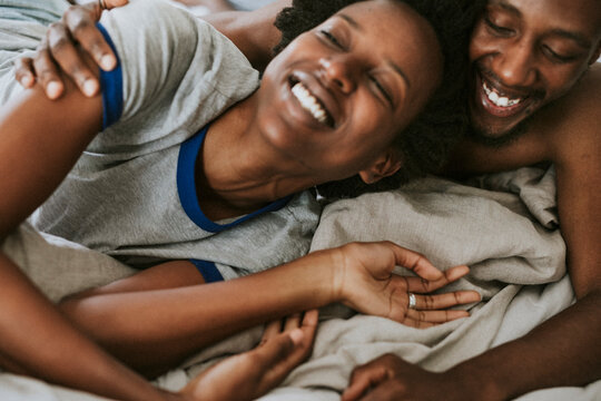 Cute happy black couple playing in bed
