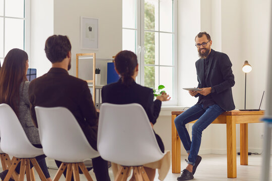 Supportive coach or team leader communicating with company employees during meeting in office