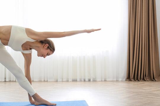 Young woman practicing triangle asana in yoga studio. Trikonasana pose