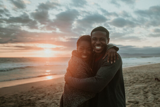 Cheerful couple hugging at the beach