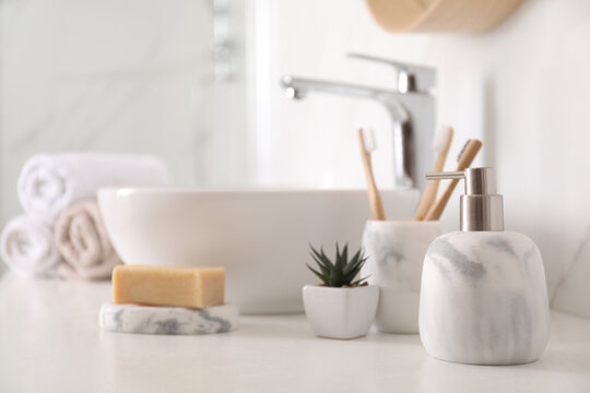 Holder with toothbrushes, plant and different toiletries near vessel sink in bathroom