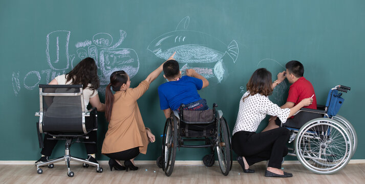 Group of special students in classroom, a down syndrome girl, two handicapped boys and  two female teachers drawing and painting on black board together