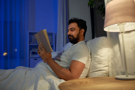 people, bedtime and rest concept - indian man reading book in bed at home at night