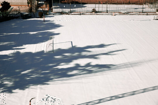 empty snow covered soccer field in winter
