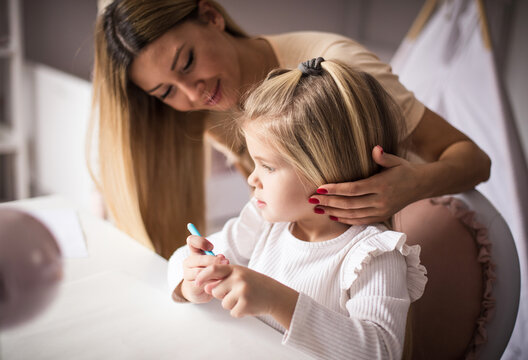 Mother and daughter in bedroom. Little girl drawing.