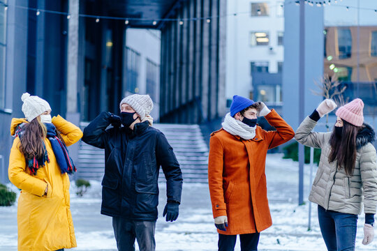Group of four people friends in facial masks bump their elbows instead of greeting with a hug in winter time outdoor. Avoid the spread of coronavirus, social distance and friendship concept.