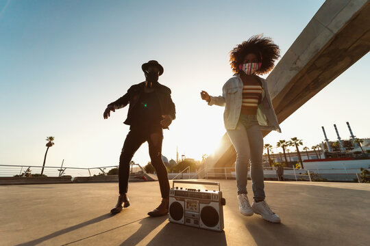 Young Afro friends wearing face mask dancing outdoor while listening to music with wireless headphones and vintage boombox