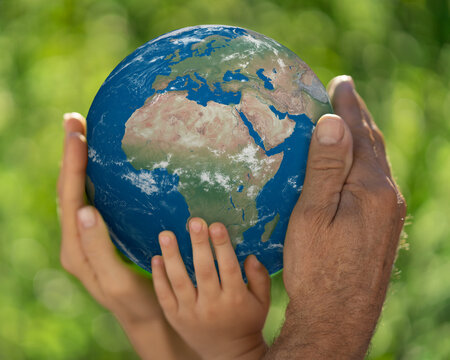 Family holding blue planet in hands. Earth day spring holiday concept. Elements of this image furnished by NASA