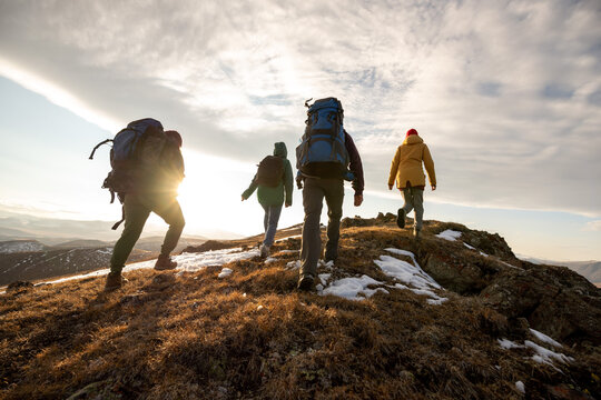 Hikers with backpacks walks in mountains at sunset