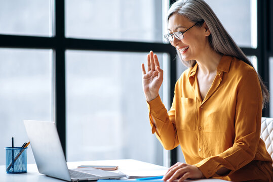 Female business woman or tutor. Smiling asian gray-haired senior woman is talking online uses a laptop for virtual online meeting, greeting colleagues while video conference, waves hand. Online