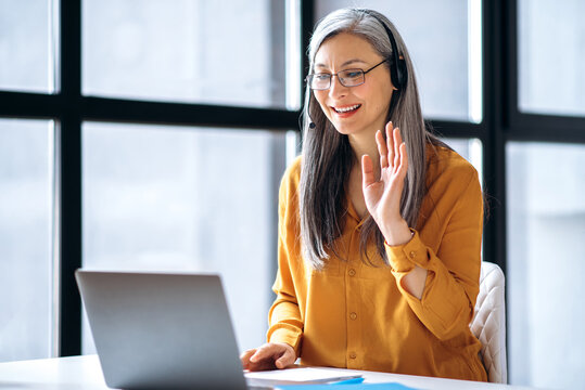 Friendly asian senior woman is talking online uses a laptop for virtual online meeting, greeting colleagues while video conference. Online communication, distance teaching concept