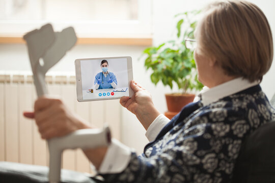 Retired senior elderly woman holding crutch and tablet computer talking to NHS GP orthopedic female doctor via virtual telemedicine video call