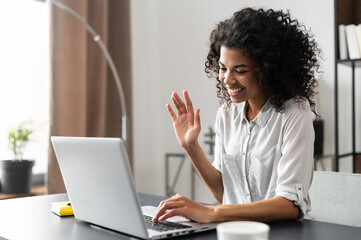 Young African American foreign language tutor starting the on-line lesson with trainee, waving,...