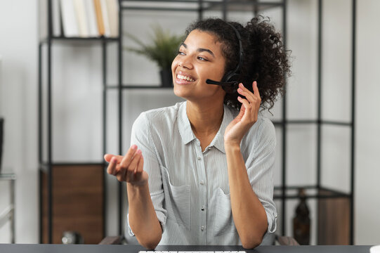Young smiley African American female customer service agent in a headset, touching microphone, talking and looking away, enjoying her work, and feeling happy to help clients and satisfy their needs
