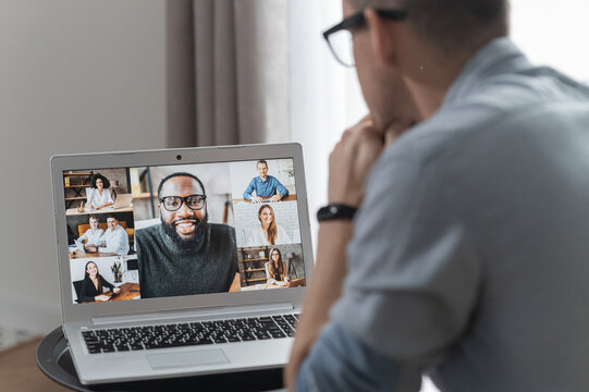 Brainstorm, online video meeting, virtual conference with multi ethnic coworkers, employee, colleagues. View over shoulder of a guy on a screen with webcam shots of diverse people