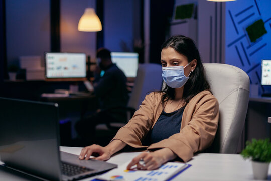 Employee with protection face mask working late at night in new normal office. Woman following social distancing rules due to coroanvirus pandemic while working late hours at the office.