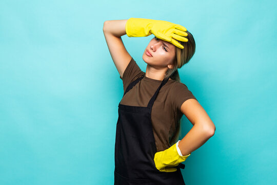 Young woman housewife hold equipment disinfection bucket clean apartment tired wear headband latex gloves apron isolated blue background