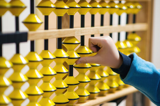 Smart kid counting on soroban abacus. Child studing at mental arithmetic school.